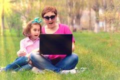 Mama i córka bawić się w laptopie outdoors Obraz Royalty Free