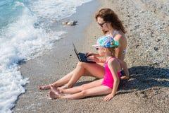 Mama i córka siedzimy na plaży fotografia royalty free