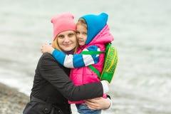 Mama i córka w ciepłej ubraniowej pozyci ręce w ręce na plaży Fotografia Royalty Free