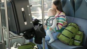 Mama i dziecko siedzimy w poruszającym pociągu blisko okno Walizka i plecaki kłaść out blisko młodej rodziny zbiory