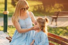 Mama i jego mała córka siedzimy na ławce w parku obrazy stock