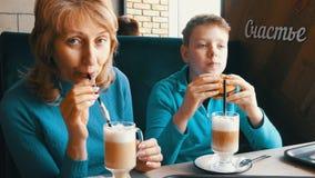 Mama i jej syna nastolatek szczęśliwi w kawiarni, matka napojów latte i synu, przez słomy jemy hamburger zbiory