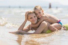 Mama i siedzi na ona z powrotem dziecka lying on the beach w wodzie na piaskowatej plaży i spojrzenie w ramę szczęśliwie Zdjęcia Royalty Free