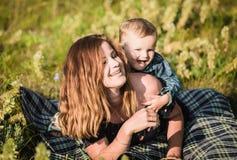 Mama i syn bawić się kłamać na dywaniku w naturze Fotografia Stock