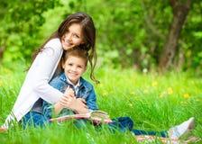 Mama i syn z książką w zieleń parku Zdjęcia Royalty Free