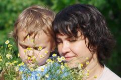 Mama joven con su hijo entre las margaritas del verano Foto de archivo