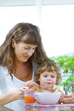 Mama meal. Portrait of young woman feeding her baby daughter Royalty Free Stock Images