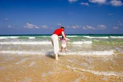 Mama mit dem Kind auf dem Meer Stockbilder