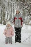 Mama mit einer Tochter unter Schnee Stockfotos