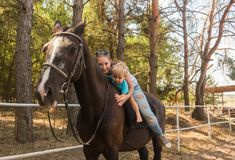 Mama mit Sohn-Antrieb auf Pferd Stockfotos