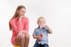 Mama ogląda jej syna dmuchać bąble Obrazy Stock
