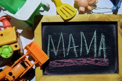 MAMA on phrase colorful handwritten on chalkboard. Loader, train bear, baby stroller with white background royalty free stock photos