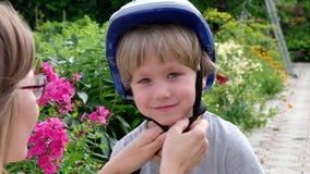 Mama pomaga jego syna stawiającego na hełmie bezpiecznie jechać rower w miasto parku zbiory wideo