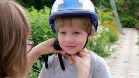 Mama pomaga jego syna stawiającego na hełmie bezpiecznie jechać rower w miasto parku zbiory
