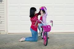 Mama pomaga jej córki przymocowywać hełm fotografia stock