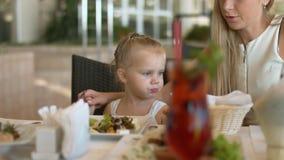 Mama pomaga jej małej córki jeść Greckiej sałatki przy restauracją zbiory wideo