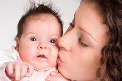 Mama que besa al bebé imagen de archivo