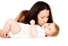 Mama que besa al bebé en la mejilla imagen de archivo