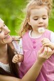 Mama que da el diente de león a la hija Fotografía de archivo libre de regalías