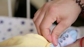 Mama stawia białe skarpety na nogach mały nowonarodzony dziecko zbiory wideo