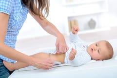 Mama stawia dalej pieluszki dziecka odmieniania stół fotografia stock