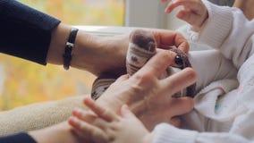 Mama stawia skarpety na nogach mały nowonarodzony dziecko zbiory wideo