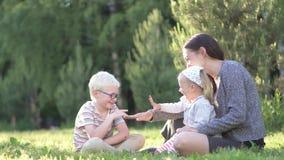 Mama, syn i mała córka, bawić się z kamienni nożyce tapetujemy w parku zbiory wideo