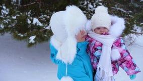 Mama trzyma jej małej córki, chodzi wzdłuż drogi w śnieżnym zimy sosny parku i śmia się Bożenarodzeniowy weekend szczęśliwa matka zbiory wideo
