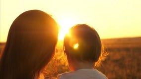 Mama trzyma jej małej córki w ona ręki szczęśliwy rodzinny dopatrywanie zmierzch na ciepłym lato wieczór w parku zbiory wideo