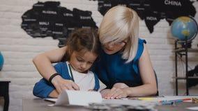 Mama uczy jej córki pisać pierwszy listach Nauczyciel i uczeń wykonujemy pracę domową w szkole podstawowej Młoda blondynka zdjęcie wideo