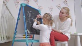 Mama uczy małej dziewczynki remis z kredą na blackboard zbiory wideo