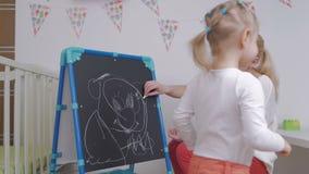 Mama uczy małej dziewczynki remis z kredą na blackboard zbiory