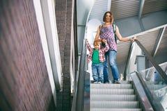 Mama und der Sohn, der auf eine Rolltreppe im Einkaufszentrum geht Lizenzfreie Stockbilder