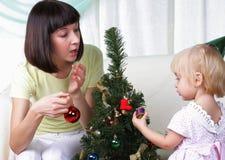 Mama und ihre Tochter verzieren einen Weihnachtenc$pelzbaum Lizenzfreie Stockbilder