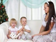 Mama und Kinder sitzt nahe einem Weihnachtenc$pelzbaum Lizenzfreie Stockfotografie