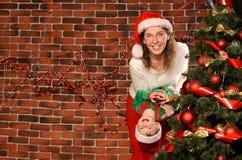 Mama und kleiner Sohn, die am Weihnachtsbaum spielen Lizenzfreies Stockfoto