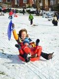 Mama und Sohn im Schlitten, der schneebedeckten Hügel, Winter schiebt Stockfotos