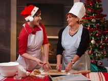 Mama und Tochter, die am Weihnachtsbacken lachen Lizenzfreie Stockfotos