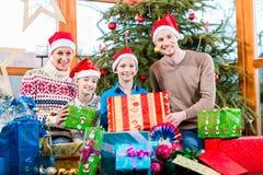 Mama, Vati und Söhne auf Weihnachten während des Austeilens von Geschenken lizenzfreie stockfotografie