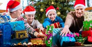 Mama, Vati und Söhne auf Weihnachten während des Austeilens von Geschenken lizenzfreies stockbild