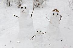 Mama, Vati und Sohn, die draußen im Winter während schwebende Zusammenfassung des Schnees falls Lizenzfreie Stockbilder