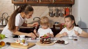 Mama wyciera jej brudnej małej córki z pieluchą podczas herbaty w domu przy stołem, rodzinny urodziny w domu zbiory