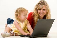 Mama y bebé con la computadora portátil Imagenes de archivo