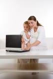 Mama y bebé que usa la computadora portátil   Fotografía de archivo libre de regalías