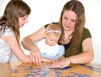 Mama y dos muchachas que hacen rompecabezas de rompecabezas Imagen de archivo