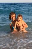 Mama y niño de la madre en el mar Foto de archivo
