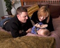 Mama y papá que cosquillean al hijo   Foto de archivo