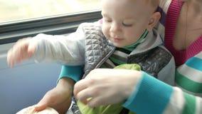 Mama z dzieckiem w poruszającym pociągu blisko okno Od plecaka, kobieta bierze out ciastko dla jej syna zbiory
