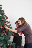Mama z jej synem dekoruje choinki Zdjęcia Stock