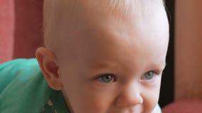Mama zieht das schöne Baby mit einem Löffelfruchtbrei ein Das Kind betrachtet einen Punkt sorgfältig Nahaufnahme stock footage